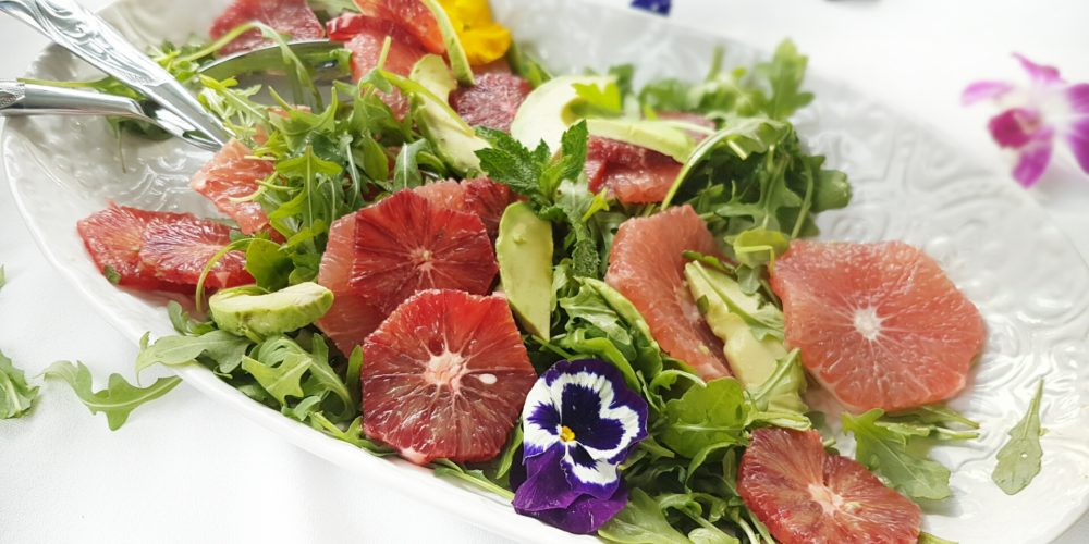 Refreshing Citrus Salad with Blood Orange and Mint placed on a white serving plate. Ingredients include mixed greens, fresh mint, oranges, grapefruit, avocado.