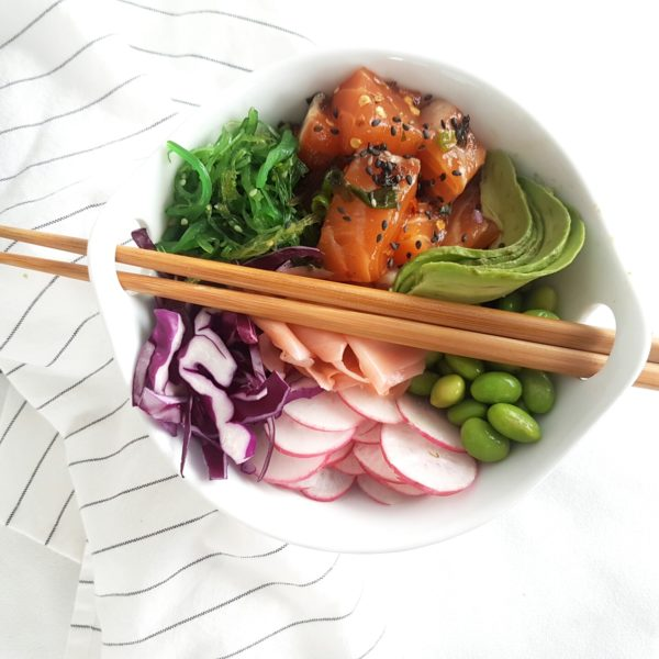 A round white bowl of rice, salmon, edamame beans, radishes, cabbage, salad on a white surface with a striped kitchen towel.