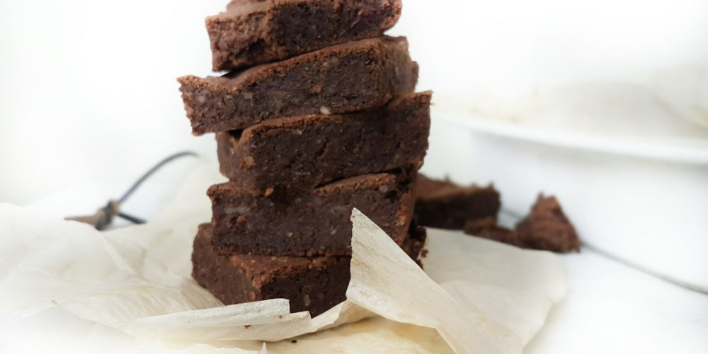 Genuine(ly) Health(ly) Sweet Potato Protein Brownies placed on a white counter on top of parchment paper. Ingredients include yam, almond meal, cacao, oat flour, vegan fermented protein, dates.