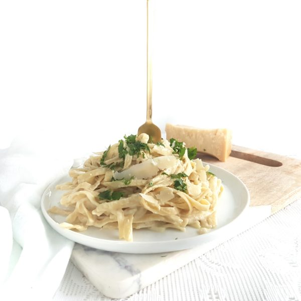 Cauliflower Fettuccini Alfredo on a round white plate placed on a cutting board with a white kitchen towel placed beside. Ingredients include fettuccini noodles, garlic, Parmesan, salt, parsley.