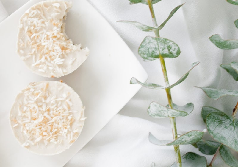Two vegan coconut cheezecakes placed on a white serving plate over a white surface with greenery. Ingredients include dates, walnuts, cashews, coconut flakes, coconut cream. lemon, sea salt, maple syrup.
