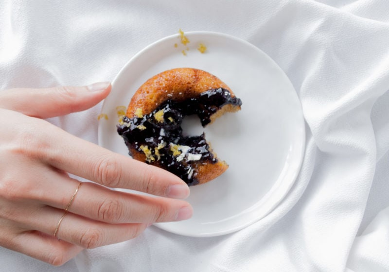 Registered Dietitian Lindsay Pleskot reaching for a donut placed on a white round plate over a white surface.