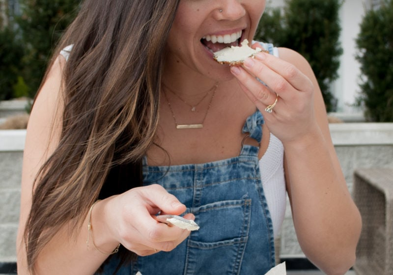 Registered Dietitian Lindsay Pleskot biting into a cracker with vegan almond feta from SPUD.