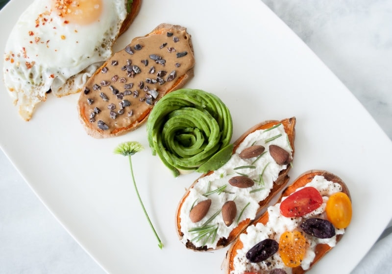 4 baked sweet potato toasts placed on a white serving plate with avocado art in the middle. Ingredients include sweet potato, peanut butter, avocado, fried egg, cottage cheese.