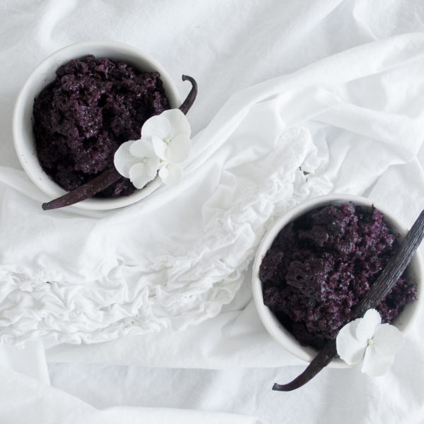 Two white bowls filled with Violet Rice Pudding on a white surface with white kitchen towels. Ingredients include violet rice, almond milk, vanilla beans.