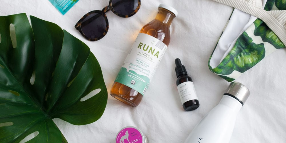 A photo of travel essentials placed on a white sheet. EnerC packets, sunglasses, Runa Tea, skin care, and a water bottle placed by a large green plant.