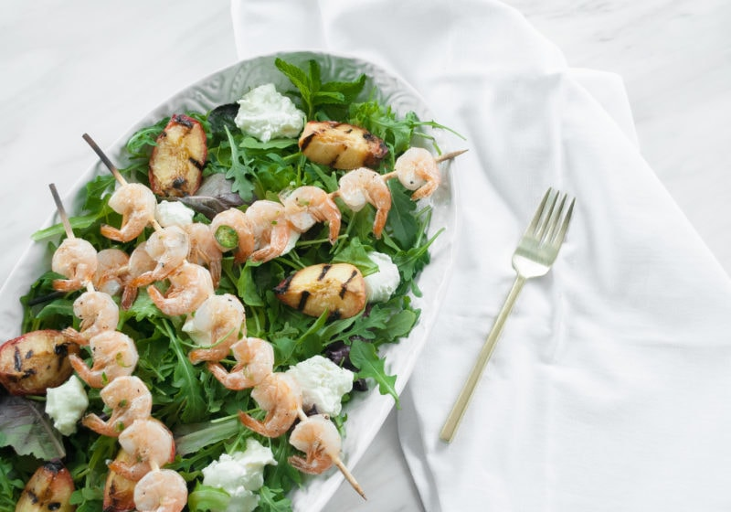 A white round serving plate topped with greens and shrimp skewers on a white surface with a white kitchen towel and fork.
