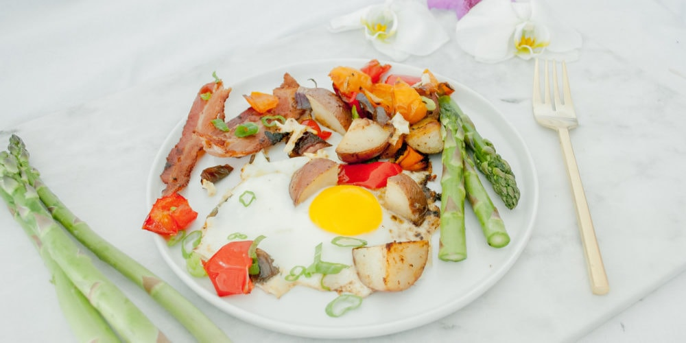 A round white plate placed on a marble cutting board with flowers and asparagus placed around. Ingredients include bacon, eggs, potatoes, bell pepper, onion, avocado oil, asparagus, pepper.