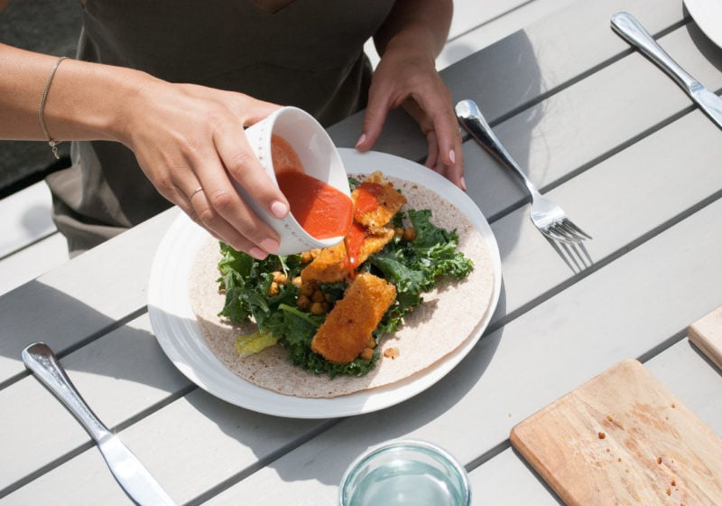 Registered Dietitian Lindsay Pleskot pouring dressing over a Buffalo Tofu Caesar Wrap outside on the patio. Ingredients include whole grain wraps, tofu, breadcrumbs, greens, hot sauce.
