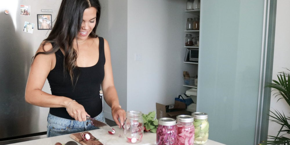 Registered Dietitian Lindsay Pleskot in the kitchen cutting radishes on a cutting board with three jars placed in front of her.