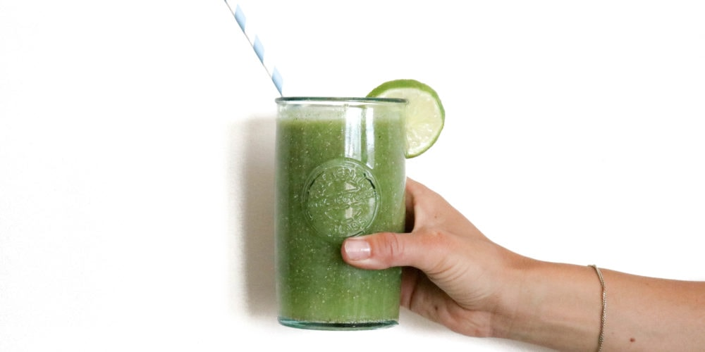 Registered Dietitian Lindsay Pleskot holding green juice with a straw and lime wedge.