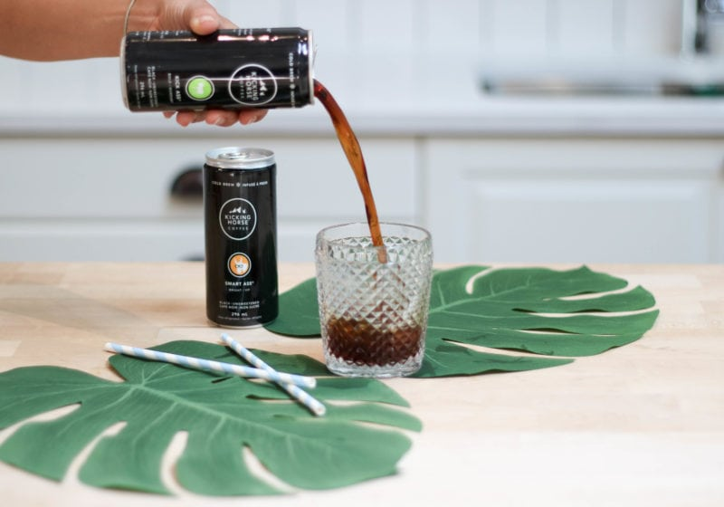 A can of coffee being poured into a drinking glass with two large leaves placed around it.