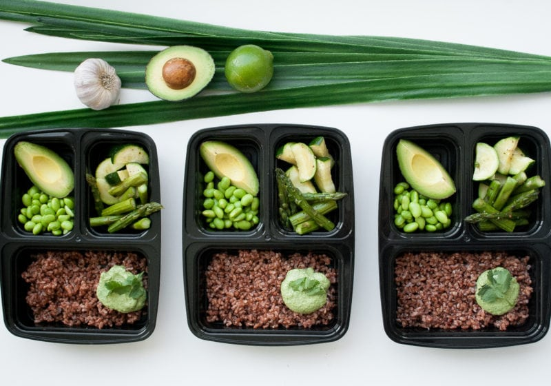 Three meal prep containers fillled with rice, avocado, edamame, asparagus, garlic, lime, leek.
