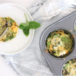 A round white plate with a frittata placed over a light blue kitchen towel and muffin tin filled with frittatas. Ingredients include egg, greens, onion, basil, cheese.