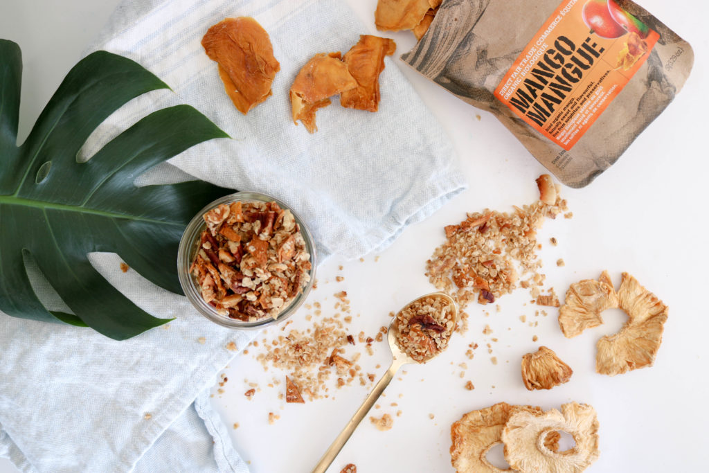 Crunchy & Nutritious Coconut Granola in a mason jar over a white surface with a light blue kitchen towel and greenery. Beside the granola is an open bag of Level Ground dried mango and a gold sppon full of granola.