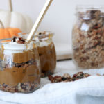 Two jars filled with Deconstructed Pumpkin Pie on a counter with a white kitchen towel and a jar of granola and pumpkins in the background. Ingredients include pumpkin, nut milk, prunes, maple syrup, vanilla.