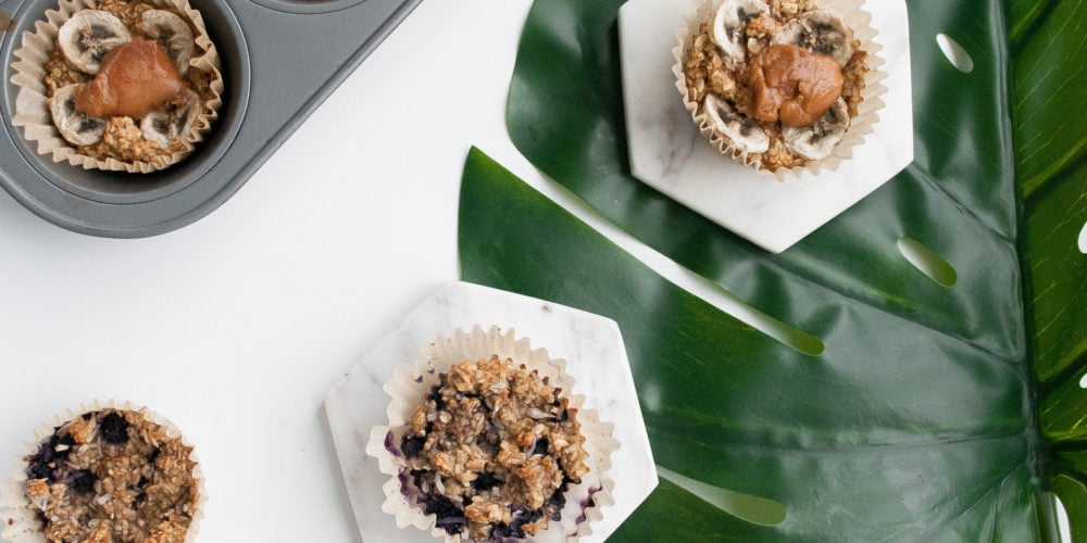 Two muffins on marble coasters on top of a green leaf on a white surface. Ingredients include banana, egg, coconut oil, rolled oats, almond milk.