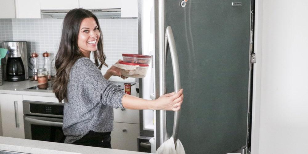 Registered Dietitian Lindsay Pleskot in the kitchen opening the fridge.