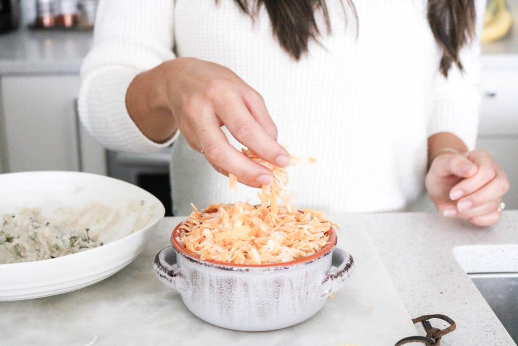 Sprinkling cheese on artichoke dip