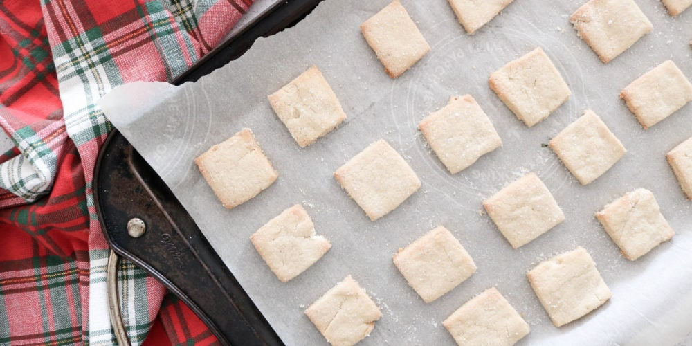 Short bread cookie squares on parchment paper placed on a baking sheet with a red Christmas kitchen towel.
