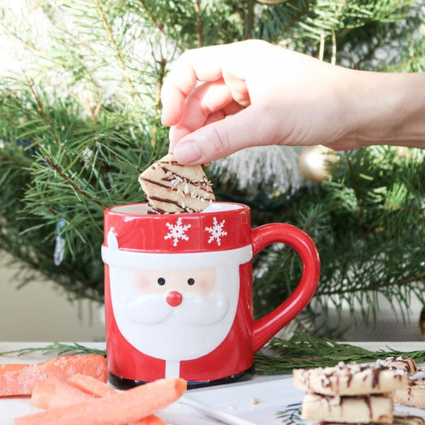 A Christmas cookie being dipped into a Santa mug.
