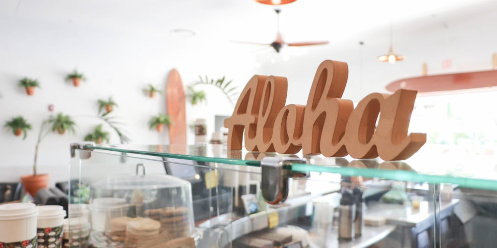 "A photo of an ""Aloha"" sign in a restaurant in Hawaii."