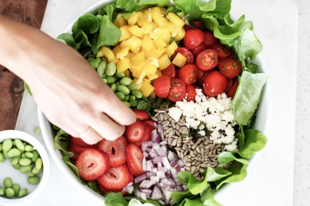 Lettuce placed in a round white bowl topped with tomatoes, quinoa, strawberries, yellow pepper, edamame beans, avocado, sunflower seeds.