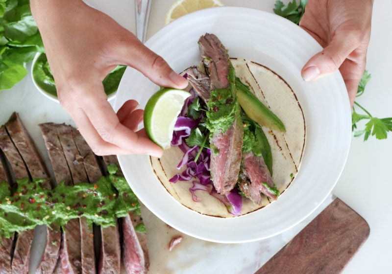 Registered Dietitian Lindsay Pleskot holding a lime wedge over a round white plate topped with grilled steak chimichurri.