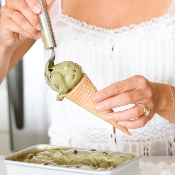 Registered Dieitian Lindsay Pleskot scooping ice cream into a cone. Ingredients include banana, mint, chocolate, greens.