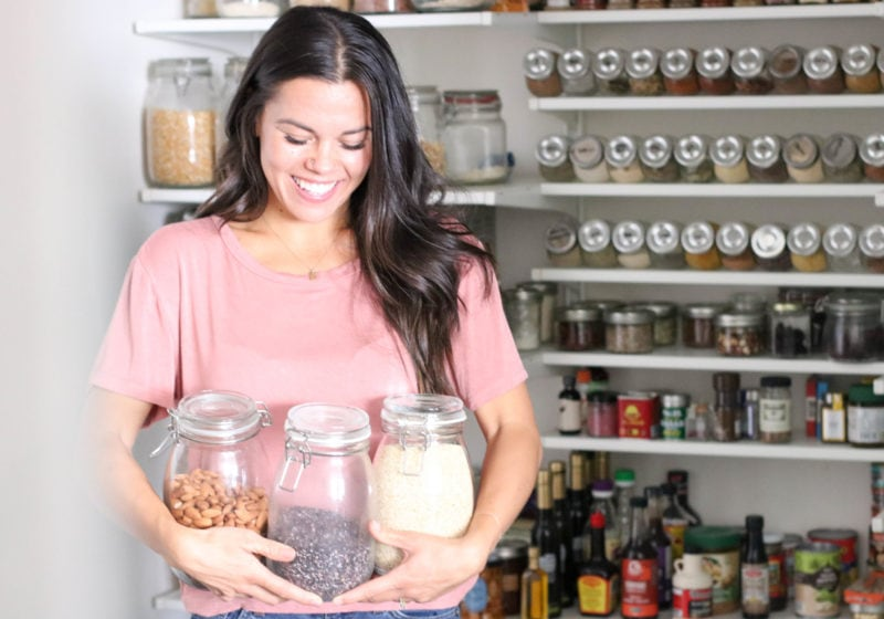 Registered Dietitian Lindsay Pleskot standing in a pantry holding three jars.