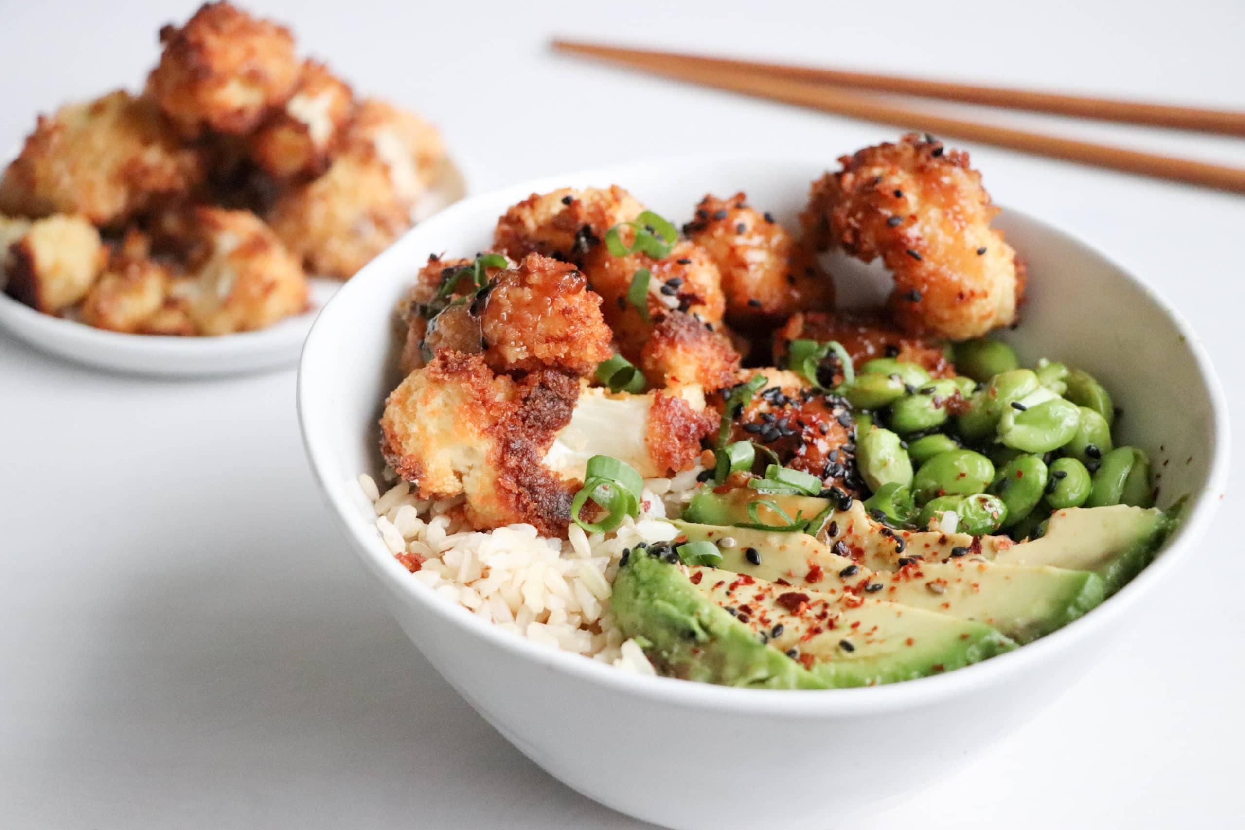 Crispy baked cauliflower in a white bowl over a white surface with a plate of crispy cauliflower beside it. Ingredients include: rice, avocado, edamame, crispy cauliflower.