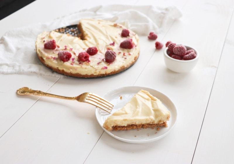 No bake white chocolate tart laid out on a white wooden food photography board. Ingredients include graham crackers, coconut oil, tofu, white chocolate chips.