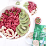 Beautiful Beet Bowl served in a white round bowl. Ingredients include beet, coconut milk, cinammon, vanilla, chia seeds, kiwi, raspberries, coconut chips, pumpkin seeds.