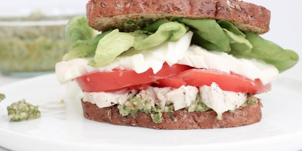 Caprese pesto sandwich made with bread, pesto, chicken, tomato, and lettuce on a white plate.