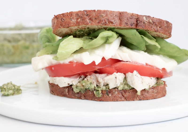 Caprese pesto sandwich made with bread, pesto, chicken, tomato, and lettuce on a white plate.