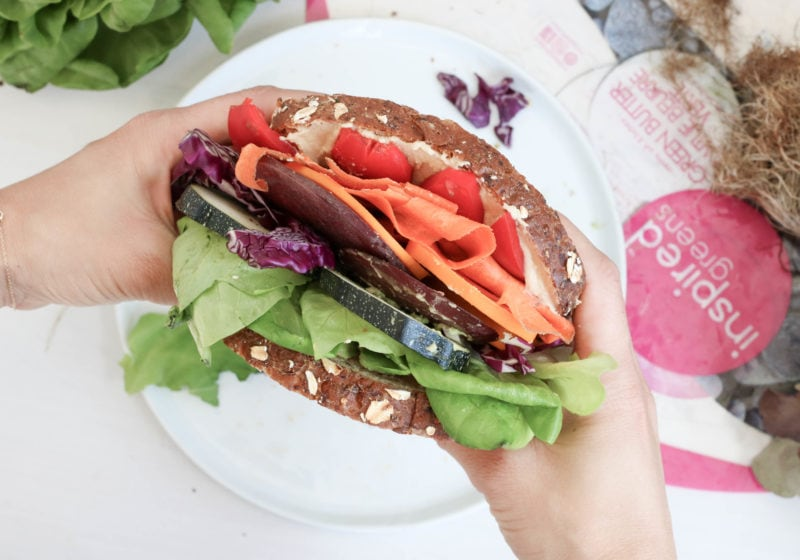 A sandwich on a white plate packed with hummus, avocado, greens, red peper, carrot, zucchini, cabbage, and red onion.