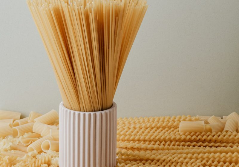 Assorted types of pasta noodles laid out on a counter with spaghetti noodle in an upright jar