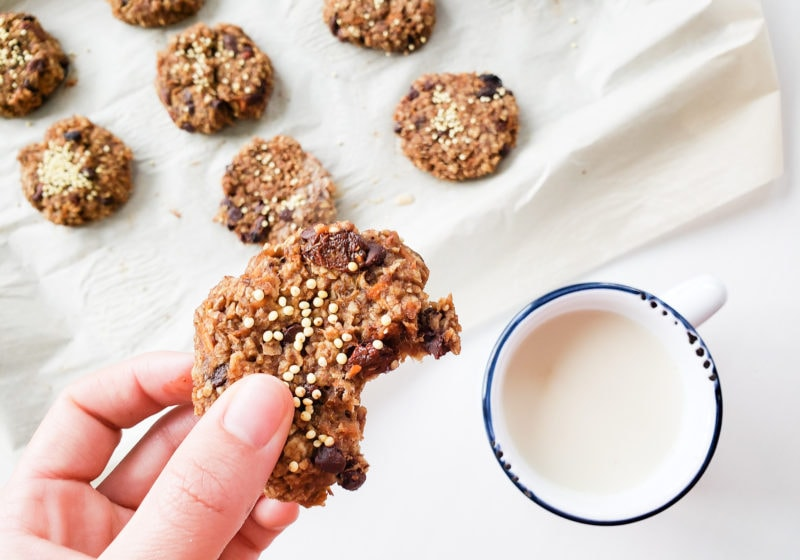 Lindsay Pleskot holding a carrot cake breakfast cookie with a white mug that has a blue rim that is filled with milk beside carrot cake breakfast cookies on baking sheet lined with parchment paper. Ingredients include carrot, apple, banana, peanut butter, maple syrup, oats, flax, raisins.
