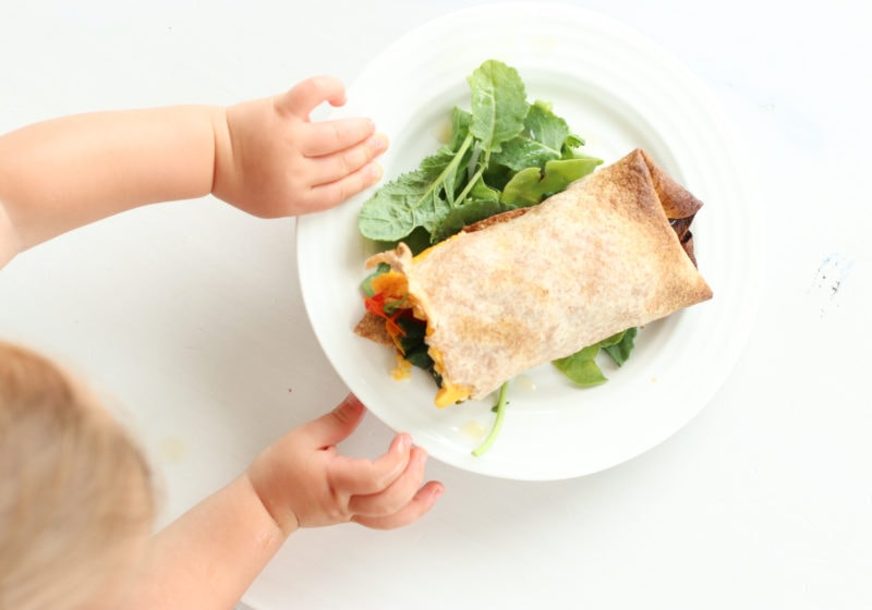 A bay's hand reaching for a breakfast burrito filled with spinach, onion, peppers, and feta