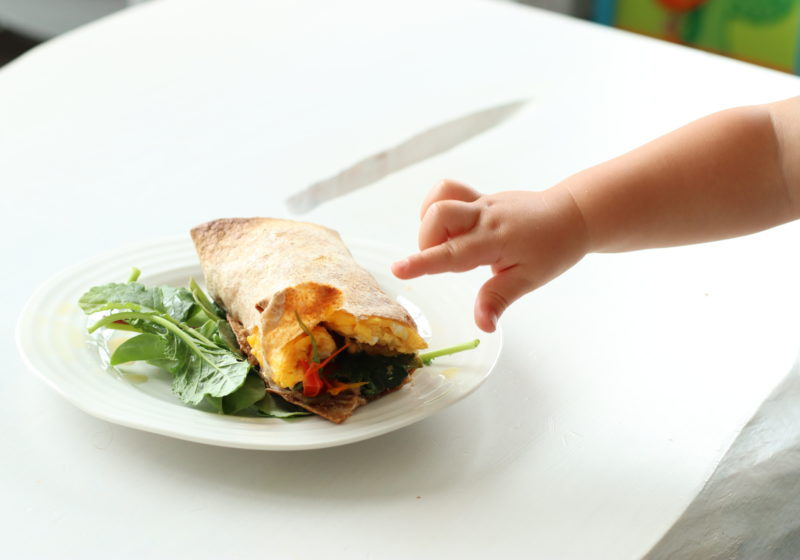a toddler's arm reaches for a breakfast burrito stuffed with eggs, peppers and spinach
