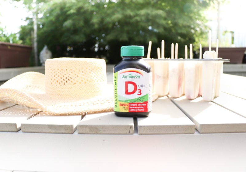 Jamieson Vitamin D3 supplement on a picnic bench with a hat and popsicles.