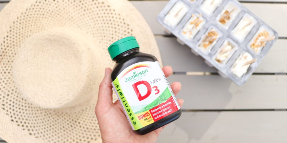 Lindsay Pleskot, RD holding a bottle of Jamieson Vitamin D supplements over a picnic bench with a hat and popsicles.