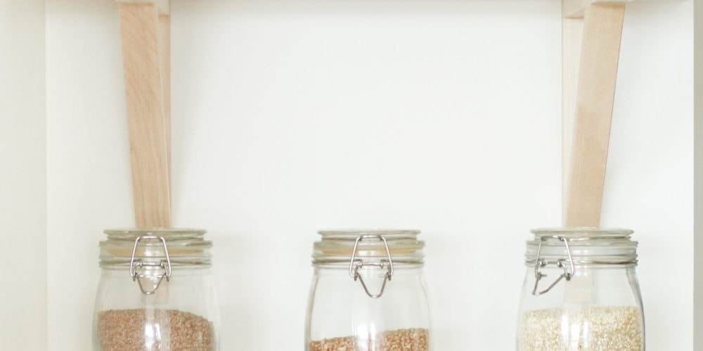 3 clear jars on a white shelf filled with grains.