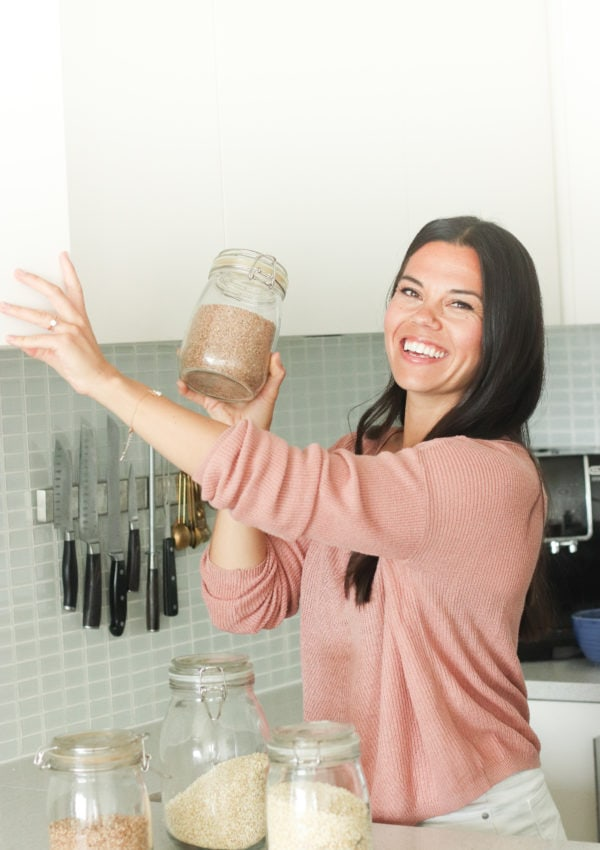 Lindsay Pleskot reaching for a clear jar of grains in her kitchen.