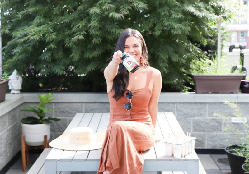 Registered Dietitian, Lindsay Pleskot, holding a bottle of Jamieson Vitamin D supplements while sitting on a picnic bench in a orange dress.