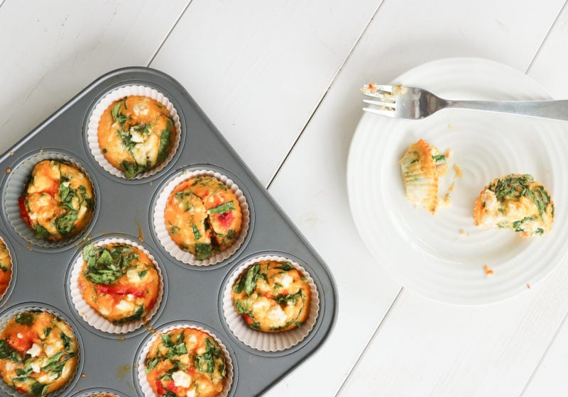 A pan of muffin tin frittatas with ingredients high in vitamin d like eggs, and smoked salmon. Another muffin tin fritatta sits on a white plate with a forkful taken out of it