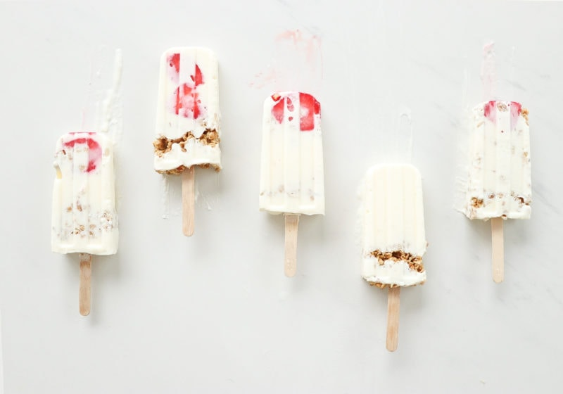 3 ingredient high protein lemon cheesecake smoothie pops laid out on a white surface.