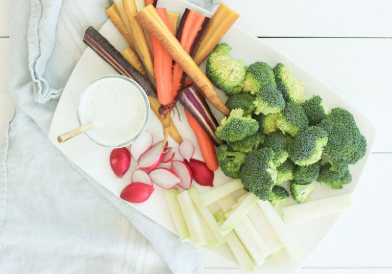 A photo of ranch yogurt dressing in a clear jar with a gold spoon and veggies such as carrots, radishes, and broccoli on a white serving plate.