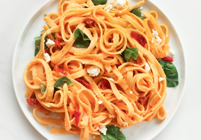 A photo of creamy red pepper pasta on a white plate. Ingredients include: fettuccine noodles, red pepper, hummust, spinach, sundried tomatoes, feta cheese.