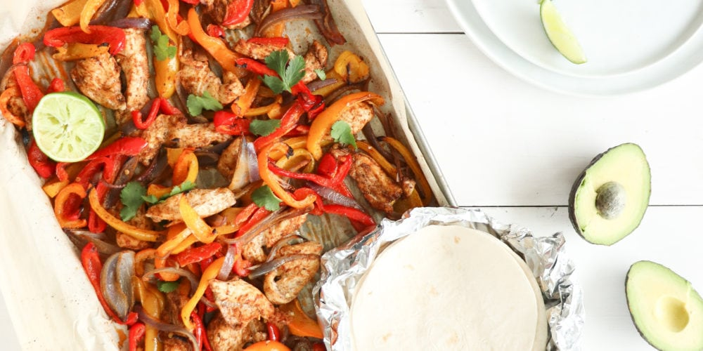 30 minute sheet pan fajitas made with simple ingredients like bell peppers, red onion, and chicken on a sheet pan over a white surface with soft shell tacos and avocados beside it.